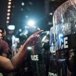 2016 - Con il sangue che copre la sua mano ed il braccio, una donna indica un agente di polizia a Charlotte, NC, USA