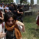 2013 - Un poliziotto turco usa del gas mentre la gente protesta contro la distruzione degli alberi in un parco sorto da un progetto pedonale, in Piazza Taksim ad Istanbul
