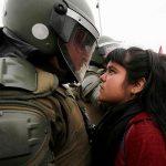 2016 - Una dimostrante affronta un poliziotto durante una protesta democratica a Santiago, Cile