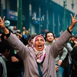 2013 - Una donna protesta e fa il segno di vittoria durante gli scontri con la polizia militare nei pressi di Tahrir Square al Cairo, Egitto