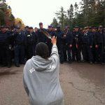 2013 - Una donna si inginocchia e tiene una piuma mentre affronta la polizia che si muove contro i manifestanti anti-fracking a New Brunswick (Canada)