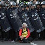 2015 - Una donna siede davanti alla polizia anti somossa, che blocca la strada, per proteggere i manifestanti durante la protesta anti-governo a Seoul, Corea del Sud