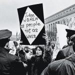1969 - Una giovane donna americana protesta per i diritti delle donne davanti alla sede centrale della Federal Trade Commission, mentre i poliziotti osservano, durante l'inaugurazione presidenziale di Richard Nixon, Washington, DC